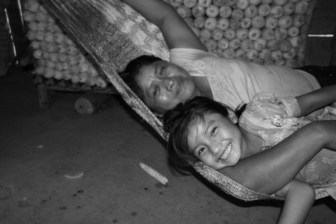 Mother & daughter cuddling in their hammock, Belize