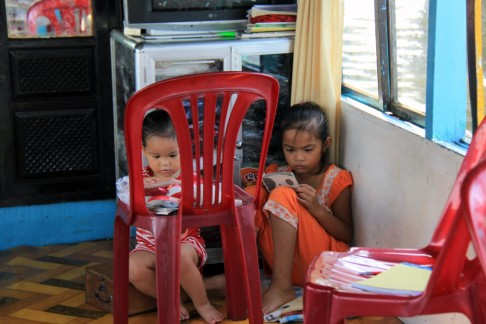 Young sisters reading on their parents' dragon boat, Song River, Hue
