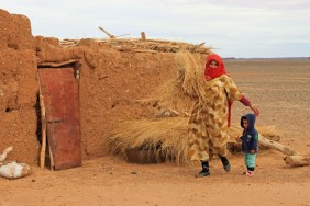 Zahra with her youngest child bringing food to her goats, Black Desert, Morocco