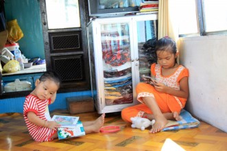 Sisters reading on their parents' Dragon Boat, Hue, Vietnam
