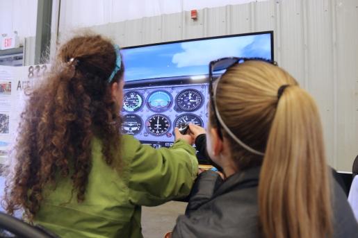 Girls at tabletop flight simulator